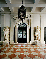 A dramatic ironwork lantern is flanked by a pair of antique statues in the communal entrance hall leading to the Venetian apartment of Lars Rachen