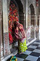 India, Dehradun.  A Woman Worshiper Prays at the Sikh Durbar Shri Guru Ram Rai Ji Maharaj Temple, built in 1707.  Visitors tie bits of red cloth to the window latticework as a symbol of prayers offered.