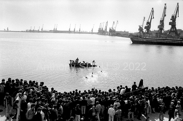 Durres, Albania<br /> February 1997<br /> <br /> Hundreds of Albanians, hoping to get a boat across the channel to Italy, steal two boats that were sitting on the port. First they dump them in the water and then they swim to it filling it up. They paddle to sea with small wooden sticks.