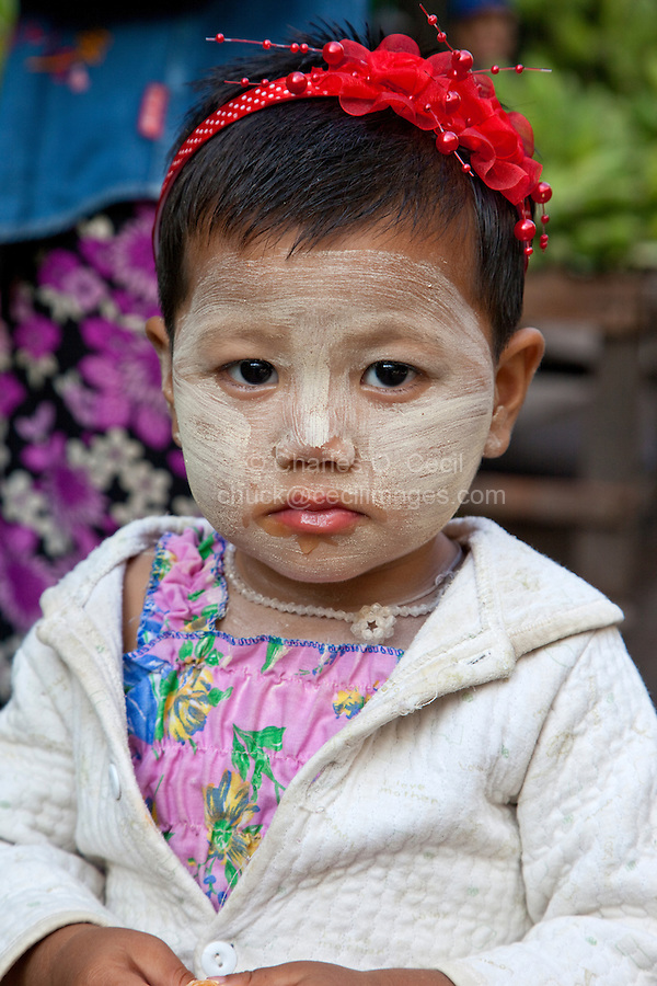 Myanmar, Burma, Mandalay.  Little Burmese Girl with Thanaka Paste on her Face, a Cosmetic Sunscreen.