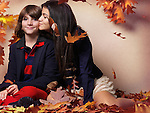 Teenage girl kissing a boy sitting surrounded with red autumn leaves artistic childrens fall fashion and lifestyle photo Image © MaximImages, License at https://www.maximimages.com
