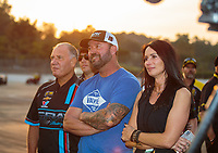 Nov 10, 2018; Pomona, CA, USA; Johnny Gray (left), Shane Gray (center) and Amber Gray react as they watch NHRA pro stock driver Tanner Gray celebrate after clinching the 2018 world championship during qualifying for the Auto Club Finals at Auto Club Raceway. Mandatory Credit: Mark J. Rebilas-USA TODAY Sports