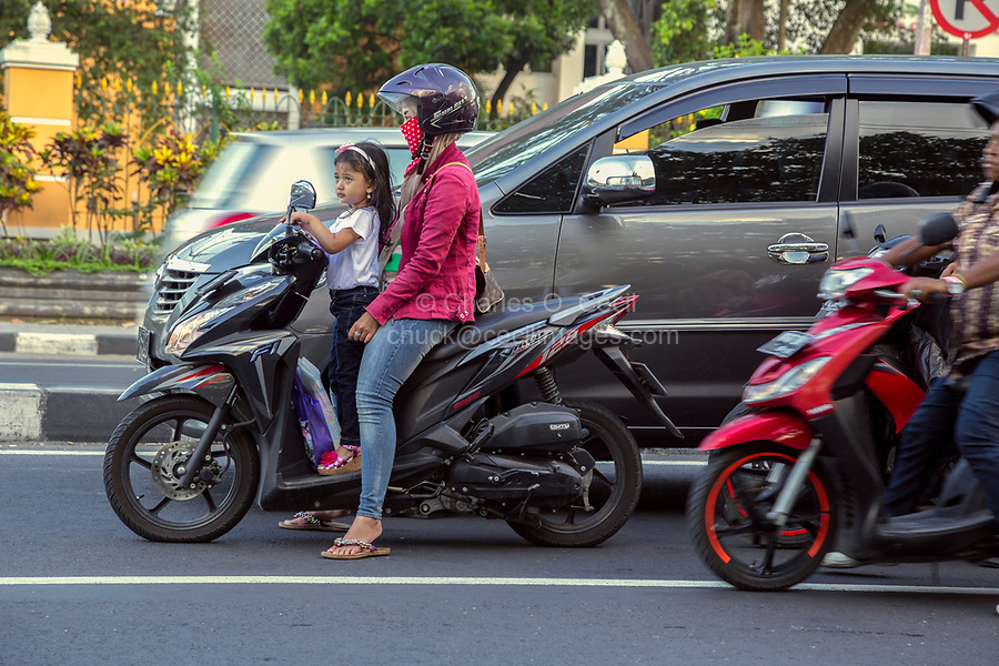 Yogyakarta, Java, Indonesia.  Evening Traffic,  Jl. Laksda Adisucipto Street.  Woman Wearing Breathing Mask.