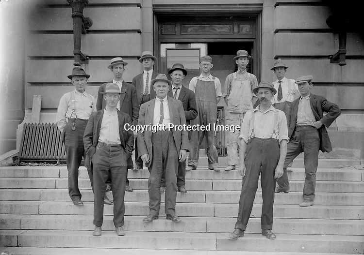 EMPLOYEES AT THE POST OFFICE, C. 1915. This mixed group appears to include office workers and other laborers. A carpenter in the back row has a hammer hanging from a loop in his overalls. The upper floors of the original building, including a handsome courtroom on the third floor, were largely unaltered during the addition of the second wing and perhaps remained in use throughout construction.<br /> <br /> Photographs taken on black and white glass negatives by African American photographer(s) John Johnson and Earl McWilliams from 1910 to 1925 in Lincoln, Nebraska. Douglas Keister has 280 5x7 glass negatives taken by these photographers. Larger scans available on request.