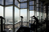 A tourist looks out onto central Shanghai from the Jinmao Tower.<br /> <br /> To license this image, please contact the National Geographic Creative Collection:<br /> <br /> Image ID: 2169233 <br />  <br /> Email: natgeocreative@ngs.org<br /> <br /> Telephone: 202 857 7537 / Toll Free 800 434 2244<br /> <br /> National Geographic Creative<br /> 1145 17th St NW, Washington DC 20036