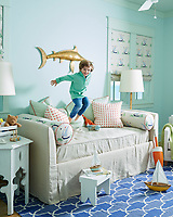 In a child's room, a sandy-hued linen daybed from Pottery Barn goes from neutral to knockout when paired with bolsters and Roman shades in Katie Ridder Beetlecat fabric, orange and green patterned throw pillows, and a vintage brass marlin from Etsy. The walls are painted Palladian Blue, and the trim is Prescott Green by Benjamin Moore. The rug is from Rugs USA.