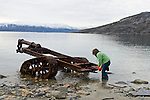 A young woman examines the remains of a rusting old machine left in the Canadian Arctic, Nunavut, Canada.