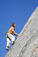Male climber on rock face against blue sky, Banff, Banff National Park, Alberta, Canada