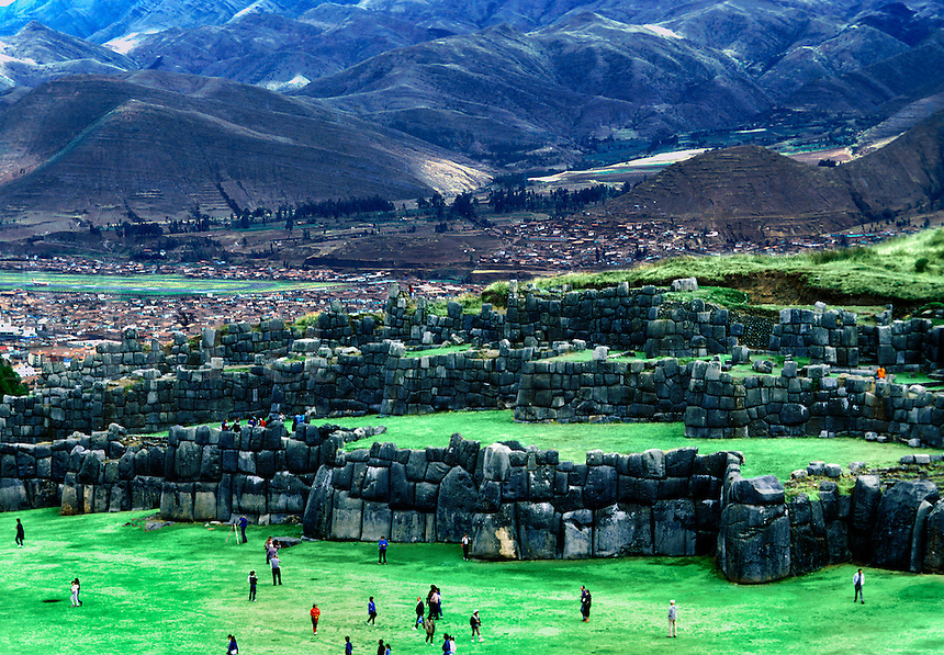 Overview of tourists visting the ruins of a wall of the fortress palace of Sacsayhuaman. Cuzco, Peru.