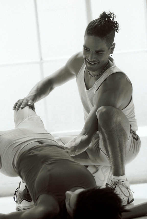 Personal training session: man assists woman with her stretching.