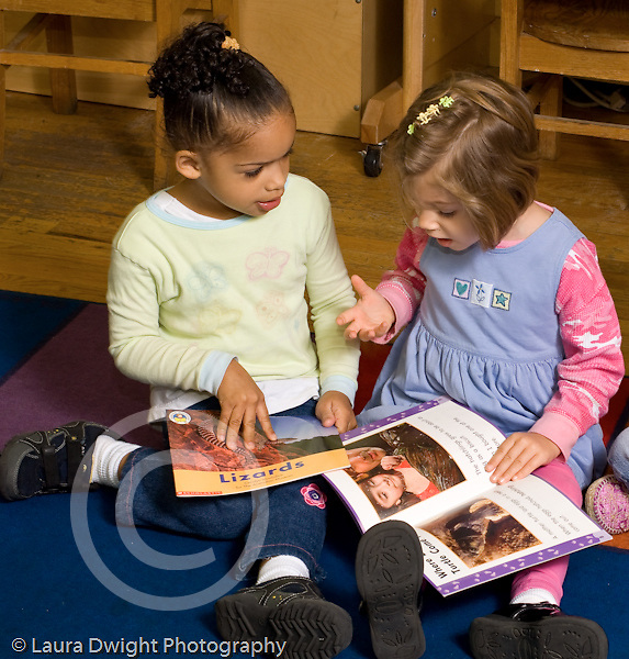 Preschool 3-4 year olds two girls sitting together talking to each other conversation looking at books
