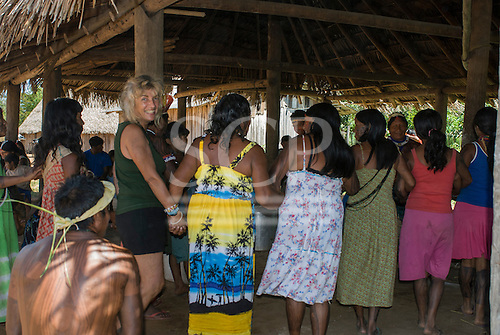 Xingu Indigenous Park, Mato Grosso State, Brazil. Aldeia Tuba Tuba (Yudja). Sue Cunningham dancing with the women around the pots of caxiri in the morning.