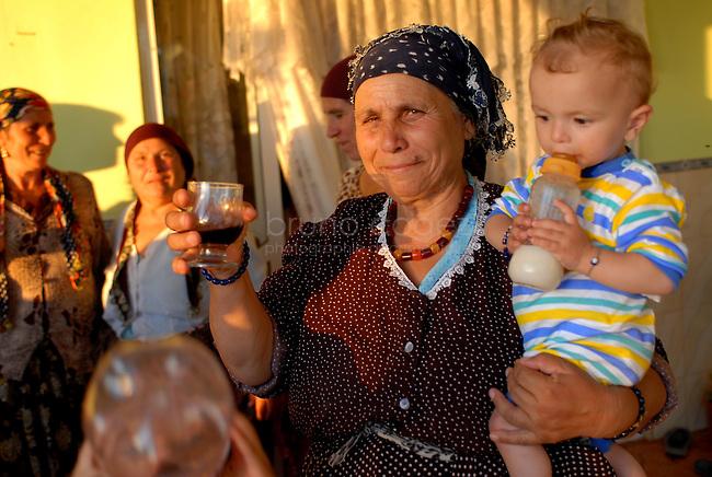 ROMANIA, Babadag, 2010/08/23.30% of the population of Babadag, a small town 15 km south of Tulcea, is composed of Muslims and Roma Horahai of Turkish origin. The colorful clothes of women are clearly distinguished from other large Roma families from Romania..© Bruno Cogez..Roumanie, Babadga, département de Tulcea 23/08/2010.30% de la population de Babadag, petite ville située à 15 km au sud de Tulcea, est composé de Roms Horahai musulmans et d'origine turque. Les vêtements des femmes très colorés se distinguent clairement des autres grandes familles roms de Roumanie..© Bruno Cogez