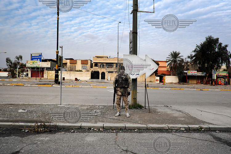 A soldier from 75th brigade of 16th division patrols a street in the Hay Ba'th neighbourhood near the Tigris River.