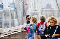 USA, New York City, Manhattan, tourists crossing the Brooklyn bridge taking photos, selfies