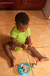 12 month old baby boy sitting on floor eating small cereal pieces, using pincer grasp