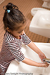 Educaton preschool  3-4 year olds girl at sink in bathroom washing hands vertical