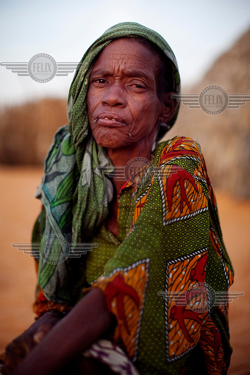 Ibrahim Mohammed's wife, who emigrated from nearby Niger, sits outside her house on top of a sand dune in the village of Tulotoluwa, which is under threat from the encroaching Sahara desert.
