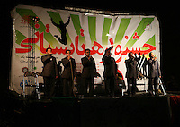 A government sponsored concert in northern tehran. the musician must sing approved songs and not move at all while preforming. Since the revolution of 1978, Iran has been living under strict Islamic rule. One law that has been enforced on iranian is banning the preformance of western music in public. Jazz, rock, hip hop, heavy metal and more have been deemed forbidden by the government. Despite threats od imprisonment, whipping and other punisments, Tehran youth defy the ban and continue to create music in underground studios. Some who are good enough are signed up by record companies overseas and eventually leave Iran for more prosperous oppportunities in the West. But some are ademant about staying in Iran and trying to build a music scene under the increasingly difficult condtions.