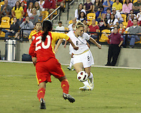 Amy Rodriguez #8 of the USA WNT takes a shot as Gaoping Zhou #20 of the PRC WNT moves in during an international friendly match at KSU Soccer Stadium, on October 2 2010 in Kennesaw, Georgia. USA won 2-1.