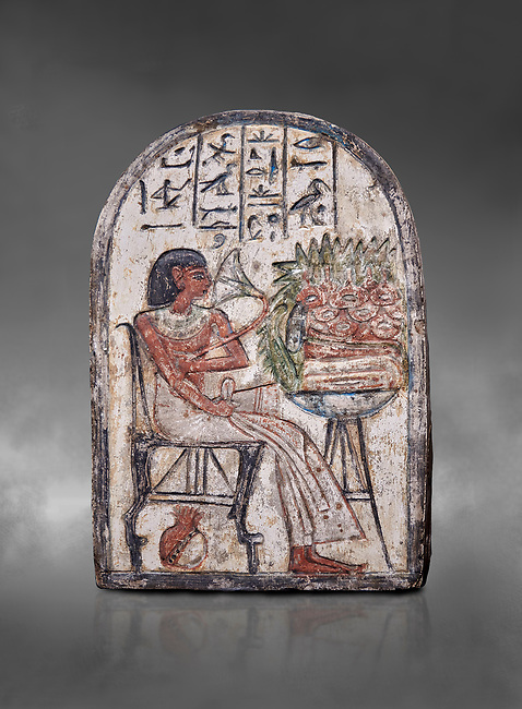 """Ancient Egyptian Ra stele , limestone, New Kingdom, 19th Dynasty, (1279-1190 BC), Deir el-Medina,  Egyptian Museum, Turin. Grey background.<br /> <br /> On this round-topped stele, the deceased Pashed, <br /> """"excellent spirit of Ra"""", akh-ikr, is pictured left, <br /> seated on a chair with lion's paws, smelling the lotus <br /> flower. The offering table holds a basket containing <br /> various offerings. A large open pomegranate, containing <br /> a great quantity of seeds, appears under the chair. The <br /> colours on this stele are well preserved.<br /> <br /> Akh iqer en Ra """" the excellent spirit of Ra' stele. The individual is smelling a lotus flower. One of three stele forund in different rooms of houses in Deir el-Medina where they stood in niches."""