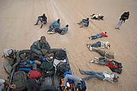 Migrants relax during a stop on their way through the desert towards the border with Algeria, to try to get to Europe in search of a better life.