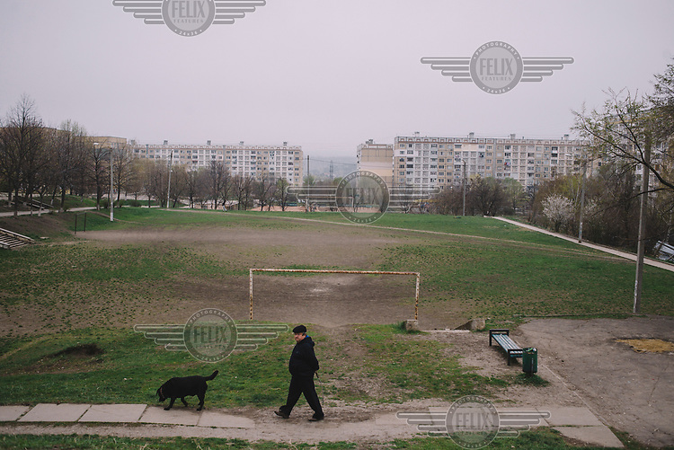 Two man walks a dog beside a football pitch in the Ciocana district.