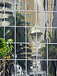 Reflexions of the tower of the Jamek mosque in a modern glassfacade, Kuala Lumpur.