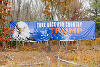 """A large campaign sign supporting the presidential re-election campaign of US President Donald Trump reading """"Take Back Our Country / Vote Nov 3 / Trump Pence"""" hangs among trees in a swampy area off of the northbound side of US Route 3 near Tyngsborough, Massachusetts, on Sun., Oct. 25, 2020. Text on the lower right portion of the sign says it is paid for by NH Citizens for Trump. The sign is close to the Massachusetts/New Hampshire border. There are other similar signs along Route 3 going northward in New Hampshire, as well."""
