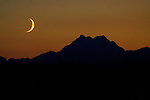 A waxing crescent moon sets over the Olympic Mountains  on Friday, July 24, 2009.In  the northern hemisphere, if the left side of the Moon is dark then the light part is growing, and the Moon is referred to as waxing (moving towards a full moon). If the right side of the Moon is dark then the light part is shrinking, and the Moon is referred to as waning (moving towards a new moon). ©2009. All Rights Reserved. Jim Bryant Photo