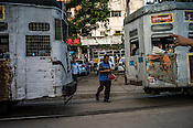 A pedestrians walks between two moving Trams at a busy intersection in Kolkata, West Bengal, India.