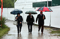 Friday 23 May 2014, Hay on Wye UK<br /> Pictured: People with umbrellas arriving in the pouring rain.<br /> Re: The Telegraph Hay Festival, Hay on Wye, Powys, Wales UK.