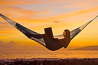 A girl uses a laptop at sunset while reclining in a hammock on Maui's west side.