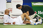 SHANGHAI, CHINA - OCTOBER 16:  Ivan Ljubicic of Croatia receives treatment from ATP trainer Hugo Gravil before retiring from his match against Rafal Nadal of Spain during day six of 2009 Shanghai ATP Masters 1000 at Qi Zhong Tennis Centre on October 16, 2009 in Shanghai, China. Photo by Victor Fraile / The Power of Sport Images
