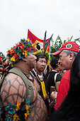 indigenous people talk with a Popular Movement demonstrator at a demonstration by indigenous people, the Landless People's Movement (MST) and other civil society groups in front of the Riocentro United Nations conference. The demonstrators are kept out of earshot and invisible to the UN conference. The United Nations Conference on Sustainable Development (Rio+20), Rio de Janeiro, Brazil, 20th June 2012. Photo © Sue Cunningham.
