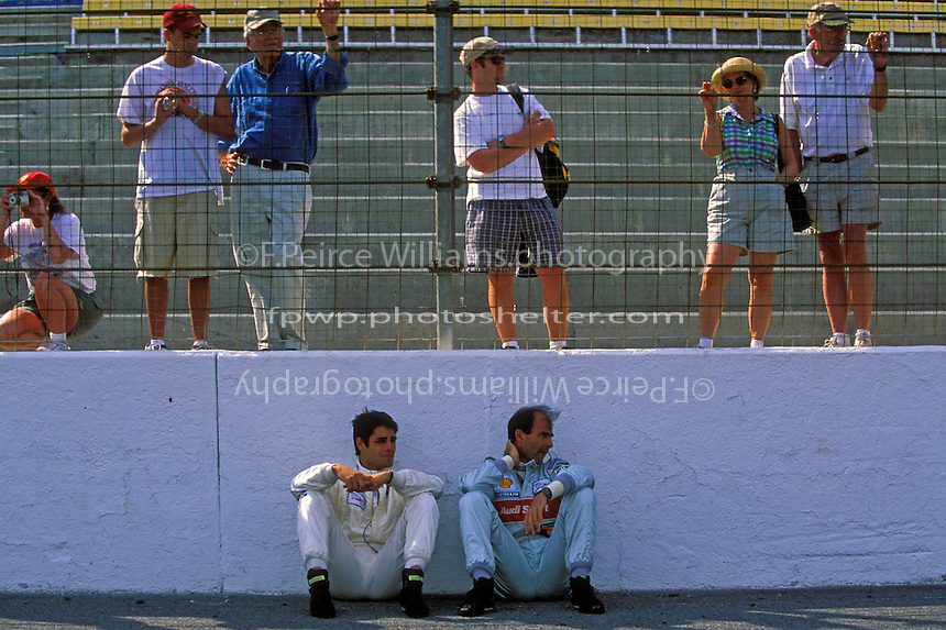 "Domenico ""Mimmo"" Schiattarella (L) and Emanuele Pirro sit in the shade of the front straight wall before the start."