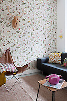 Throughout the apartment, Iris has created playful contrasts between complex patterns and simple, bold shaped furniture, such as the old fashioned bird wallpaper and retro style seating in the living room