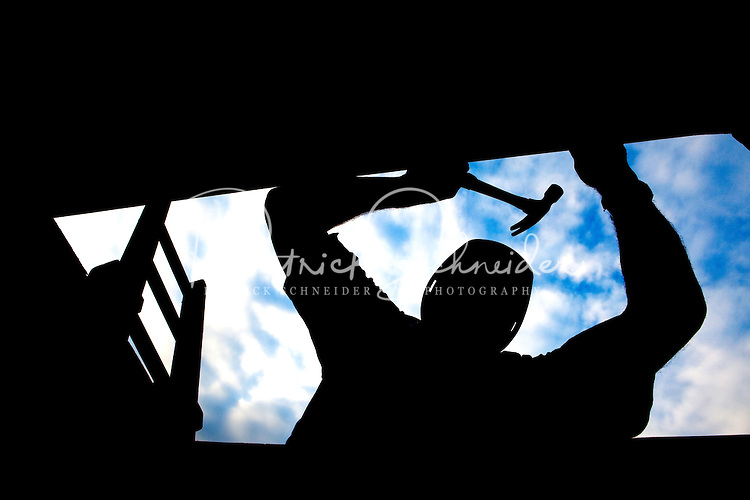 Silhouetted construction worker hammering.
