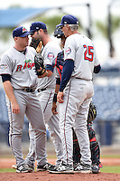 Fort Myers Miracle pitcher Brian Gilbert (35) listens to pitching coach Gary Lucas (25) as catcher Jairo Rodriguez (20) listens in with first baseman Mike Gonzales (32) in the background during a game against the Charlotte Stone Crabs on April 16, 2014 at Charlotte Sports Park in Port Charlotte, Florida.  Fort Myers defeated Charlotte 6-5.  (Mike Janes/Four Seam Images)