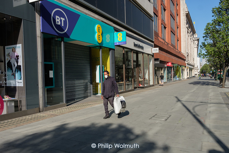 Covid-19 pandemic.  Man in a mask.  Empty pavements, closed shops and no traffic in Oxford Street, London.