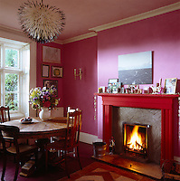 The dining room is painted a fresh pink and furnished with a circular dining table