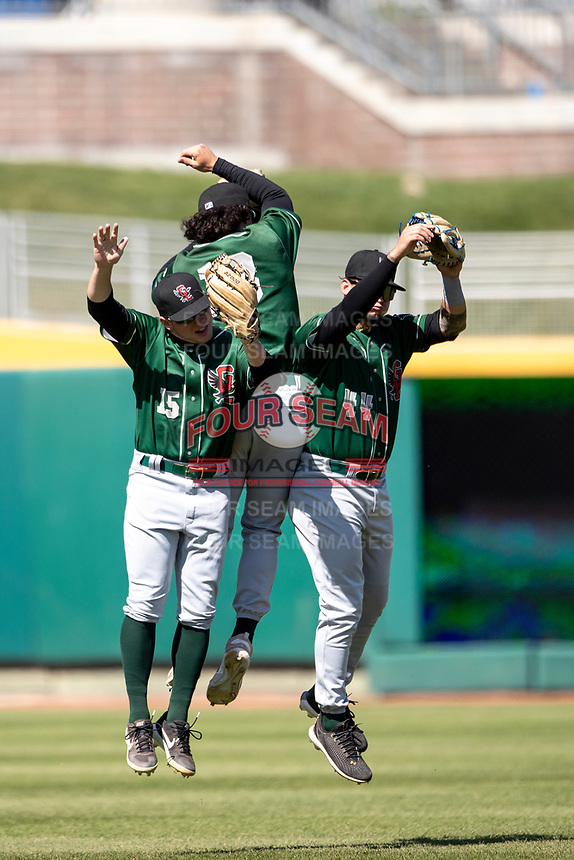 Great Lakes Loons outfielders Ryan Ward (15), James Outman (13) and Andy Pages (44) celebrate a victory on May 30, 2021 against the Lansing Lugnuts at Jackson Field in Lansing, Michigan. (Andrew Woolley/Four Seam Images)