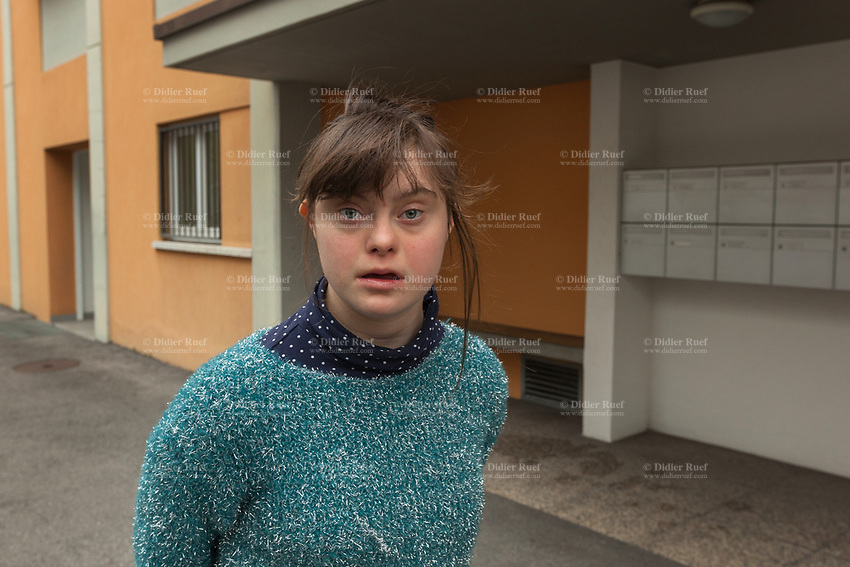 """Switzerland. Canton Ticino. Mendrisio. Fondazione Diamante. Gaia Mereu is standing outside """"Il Punto"""" which is a protected laboratory offering adults with moderate working skills or disabilities an opportunity to carry out production activities in a protected environment. Gaia Mereu is a dancing member of MOPS_DanceSyndrome which is an independent Swiss artistic, cultural and social organisation operating in the field of contemporary dance and disability. It is composed only of Down dancers. Down syndrome (DS or DNS), also known as trisomy 21, is a genetic disorder caused by the presence of all or part of a third copy of chromosome 21 It is usually associated with physical growth delays, mild to moderate intellectual disability, and characteristic facial features. 10.02.2020 © 2020 Didier Ruef"""