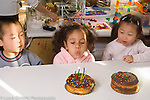 Preschool Headstart 4 year olds birthday celebration at lunch girl blowing out candles on cake, classmates looking on
