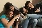 Education High School girls in corridor between classes looking at their phones
