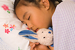 5 year old girl at home closeup horizontal asleep in bed holding favorite stuffed toy animal rabbit