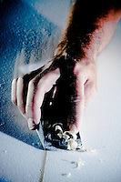 Close up of shaper Matt Yerxa's hand planing a surfboard