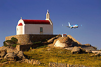 One of the hundreds of traditional  red roofed chapels on Mykonos with a plane landing, Cyclades Islads, Greece