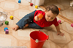 10 month old baby boy throwing wooden block into metal bucket