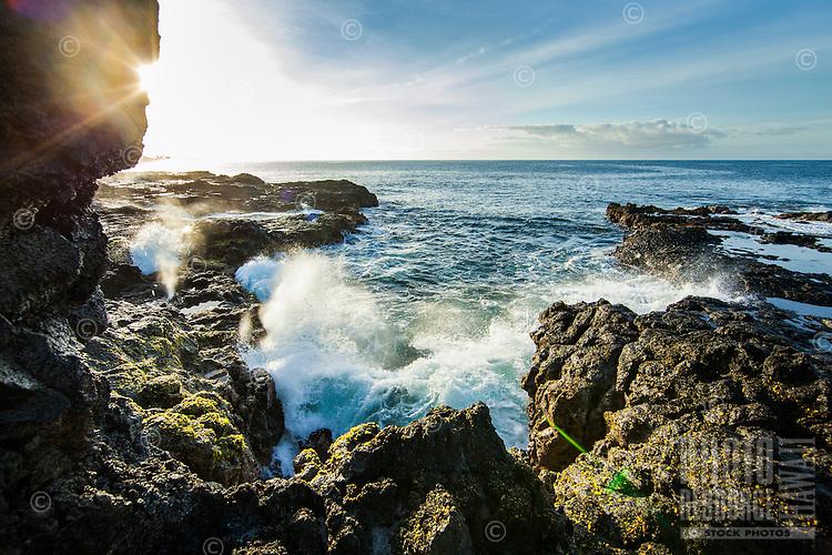 Waves crash up against lava rocks in the morning on Kaua'i.